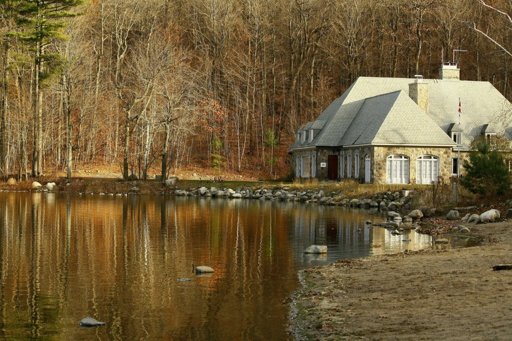 Image of a chalet next to a lake. The trees in the background are bare and leaves cover the ground; it appears to be late fall.